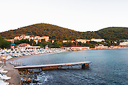 Empty Beach, jetty and hotels in evening sunlight sunset. Uvala Sumartin bay between Babin Kuk and Lapad peninsulas. Dubrovnik, new city. Dalmatian Coast, Croatia, Europe.