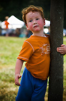 A youngster pauses at a tree after romping at the 2010 Appel Farm Arts & Music Festival in Elmer, NJ.