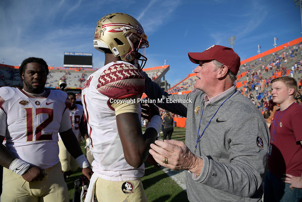 Florida State president John Thrasher, right, congratulates quarterback James Blackman (1) after an NCAA college football game against Florida Saturday, Nov. 25, 2017, in Gainesville, Fla. FSU won 38-22. (Photo by Phelan M. Ebenhack)