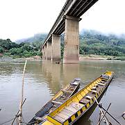 Wooden open-top boats tied to a pole on the banks of the Nam Ou (River Ou) directly under the high concrete bridge spanning the river in Nong Khiaw in northern Laos.