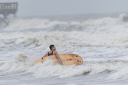 October 7, 2016 - Isle Of Palms, United States - A surfer struggles with strong tides and winds as Hurricane Matthew approaches the coast October 7, 2016 in Isle of Palms, South Carolina. The hurricane is expected to make landfall near Charleston as a Category 2 storm with strong winds, rain and storm serge. (Credit Image: © Richard Ellis via ZUMA Wire)