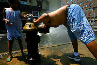 George Byron cools off in a fire hydrant  at the corner of Lexington and 119th Street in Manhattan as Yvette Jones looks on.Temperatures reached triple digits in Manhattan today.