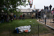 Royalist enthusiasts camp outdoors in the Mall, in the hours before the royal marriage of Prince William and Kate Middleton. A man dozes in his sleeping bag with Buckingham Palace in the background while a massed crowd of Britons and foreign visitors (many Americans and Commonwealth citizens)  who are asleep in small tents and warm under sleeping bags. Taking place on Friday 30th April in front of millions the crowds are already gathering to claim their ideal locations in the front rows along the procession route later that morning.