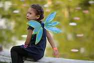Old Westbury, New York, U.S. - June 21, 2014 - Sitting at the edge of the Reflecting pool is one of many young girl visitors dressed in fairy costumes to see the Lori Belilove & The Isadora Duncan Dance Company dance throughout the gardens during the Midsummer Night event at the Long Island Gold Coast estate of Old Westbury Gardens on the first day of summer, the summer solstice.