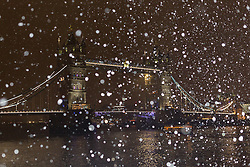 © Licensed to London News Pictures. 12/01/2017. LONDON, UK.  Snow flurries fall on Tower Bridge this evening during cold winter weather, as the temperatures drop.  Photo credit: Vickie Flores/LNP