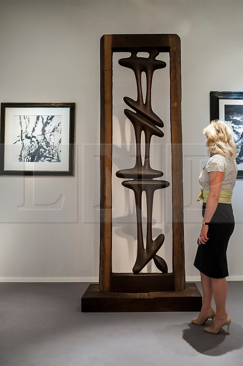 "© Licensed to London News Pictures. 24/06/2015. London, UK.   A visitor looks at Agustin Cardenas' ""La Porte / The Door"", at the preview of Masterpiece London, the international cross-collecting Fair for art, antiques and design which takes place at The Royal Hospital Chelsea 25 June to 1 July. Photo credit : Stephen Chung/LNP"