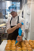 A baker piping cream into fresh doughnuts at Offbeat Donut Co on 3rd April 2017 in Dublin, Republic of Ireland. Dublin is the largest city and capital of the Republic of Ireland, it's on Ireland's east coast at the mouth of the River Liffey.