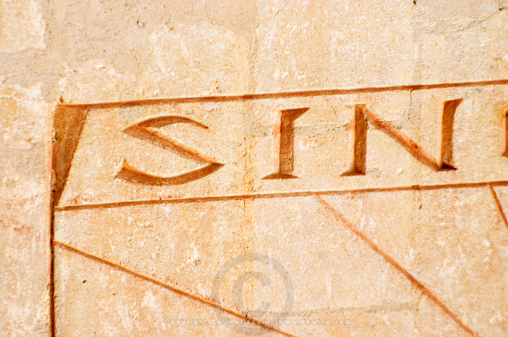 The sun dial on the wall of the building with the carved stone inscription 'Sine Sole Nihil', without the sun there is nothing. Detail showing just the text 'sin' Chateau Mourgues du Gres Grès, Costieres de Nimes, Bouches du Rhone, Provence, France, Europe