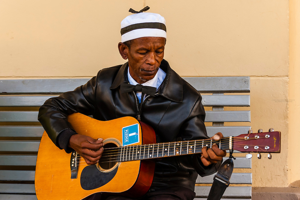 """A local man plays guitar at the train station at Matjiesfontein, Rovos Rail train """"Pride of Africa"""" on it's journey between Pretoria and Cape Town, South Africa."""