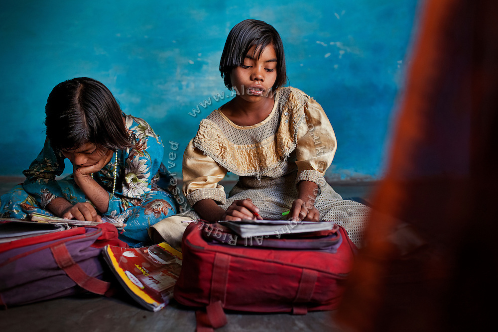 Poonam, 10, (left) and her older sister Jyoti, 11, (right) are studying together while sitting inside their family's newly built home in Oriya Basti, one of the water-contaminated colonies in Bhopal, central India, near the abandoned Union Carbide (now DOW Chemical) industrial complex, site of the infamous '1984 Gas Disaster'.