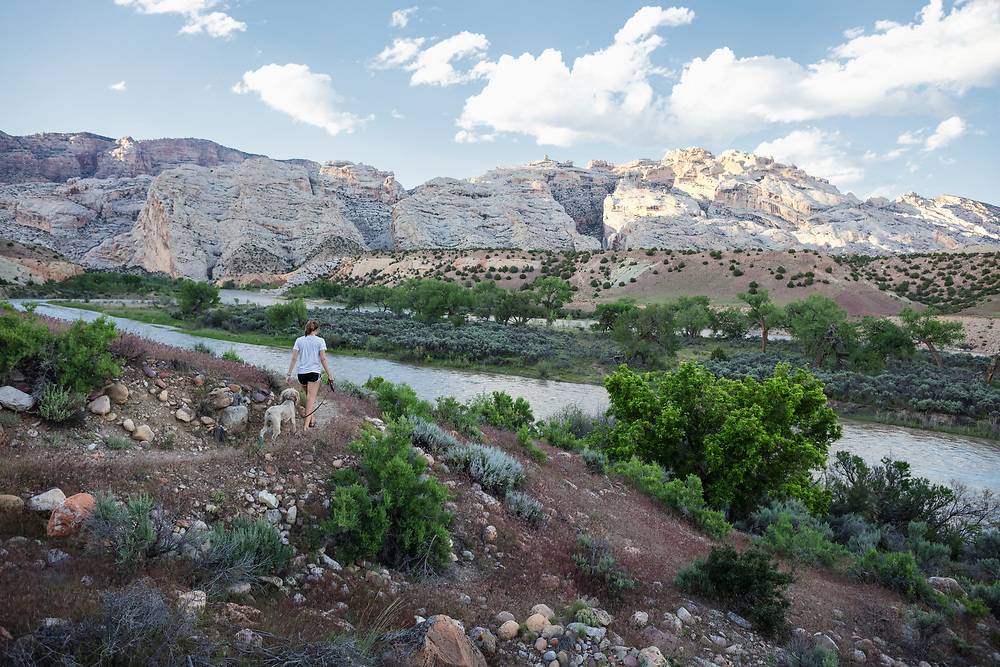 Young woman and dog hike along the River Trail in Dinosaur National Monument in Utah