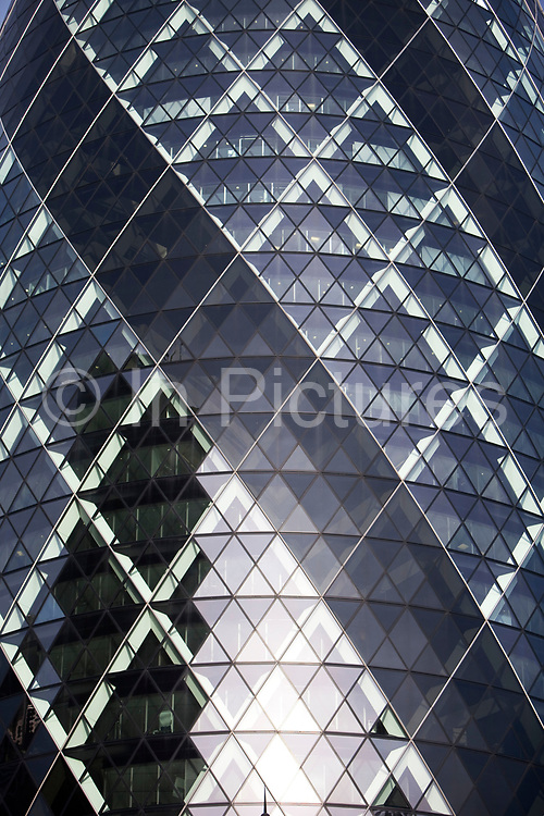 Detail of the Gerkhin. 1 St Mary Axe, also knowns as The Gherkin in the City of London. This iconic building is one of the best loved buildings in London with it's distinctive bullet like shape and twisted glass exterior.