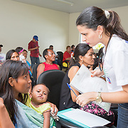 CAPTION: At Hospital Geral de Benjamin Constant, a nurse talks to a lady and her child in the local indigenous language, gathering information about the various cleft patients who've come to see the team of doctors from Manaus. LOCATION: Hospital Geral de Benjamin Constant, Rua 13 de Maio, 1496, Benjamin Constant, Amazonas, Brazil. INDIVIDUAL(S) PHOTOGRAPHED: Maria Turibio (mother wearing yellow), Lilás Turibio (her baby) and Alessandra Maciel (standing).