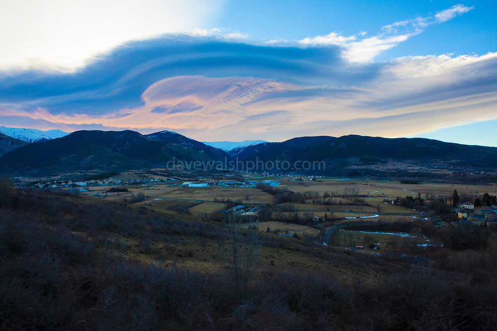 Lenticular Clouds near Saillagouse, on the Spain/France border of Catalonia. Clouds like these more or less stationary and lens-shaped,  forming in the lower atmosphere, usually perpendicular to wind direction. Where I took this image was quite cold - the other side of the mountains, warm air was blowing in from the Mediterranean Sea - with the combination of both, the vapour was likely formed.