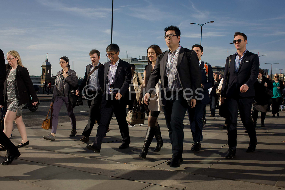 Londoners cross southbound over London Bridge during the evening rush hour. Wearing office lanyards, business people of Asian descent stride along followed by others walking out of the City of London. There has been a crossing over the Thames here since the Romans first forded the river in the early 1st Century with subsequent medieval and Victorian stone bridges becoming an important thoroughfare from the City on the north bank, to Southwark on the south where transport hubs such as the mainline station gets commuters to the suburbs and satellite towns.