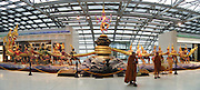 """Buddhist monks stand by the impressive sculpture of the Churning of the Milk Ocean. The artwork was relocated elswhere in 2008 as it was too big (30 meters wide and 5.5 meters high) for the fire regulations of Suvarnabhumi Bangkok Airport (pronounced """"Su-Wana-Poom"""" in Thai, meaning """"The Golden Land""""). The Churning of the Milk Ocean (or Sagar Manthan; Samudra Manthan; Samudra manthanam; or Ksheersagar manthan) is one of the most famous episodes in Sanskrit literature, appearing in the Srimad Bhagavatam, the Mahabharata and the Vishnu Purana. Demons and gods cooperate to churn the sea for thousands of years in order to bring forth missing treasures after the recreation of the universe, including the heavenly nectar of immortality (amrita). The King Power Group donated this 48-million-baht art sculpture to the Airport. Image published 2010 by Institute of Southeast Asian Studies (ISEAS), Singapore. Panorama stitched from 2 overlapping images."""