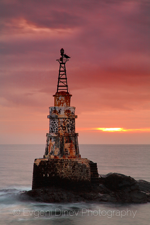Old lighthouse in a stormy sea at sunrise