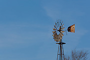 A windmill stands in the mid-day sun on an Iowa winter afternoon.