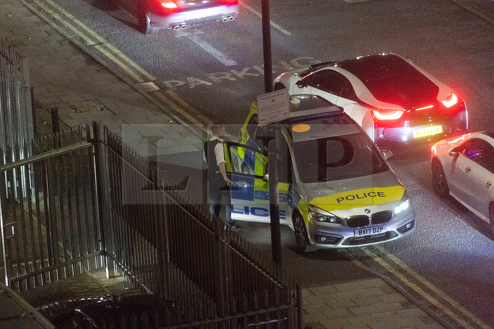 © Licensed to London News Pictures. 27/11/2020. London, UK. A Police car blocks the entrance of an industrial estate hosting a car enthusiasts sports car rally meeting in Alperton, North-West London during the second Covid-19 lockdown. The police officers later disbursed the drivers. Photo credit: London News Pictures