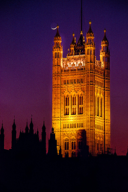 The moon rises above the Houses of Parliament, London, England