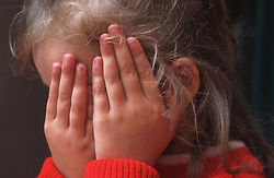 Young girl covering face with hands,