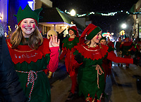 """Vanilla and Sparkey Santa's elves from Christmas Village are all smiles as they march in the snow during the """"Light Up Laconia"""" Holiday Parade on Sunday evening.  (Karen Bobotas/for the Laconia Daily Sun)"""