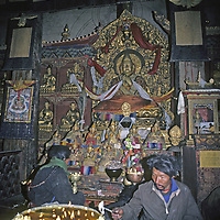 CHINA, TIBET, LHASA. Tibetan Buddhist devotees pray and make yak butter offerings at chapel inside Jokhang Temple, holiest site in Tibet.