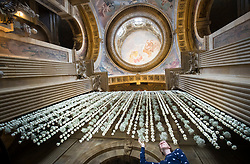 """Castle Howard employee Hannah Cooke puts the finishing touches to a """"waterfall"""" of 3000 white carnations in the Great Hall ahead of the Castle Howard in Bloom Flower Festival in Yorkshire."""