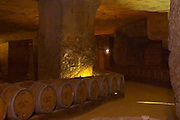 The underground winery and cellar in an old stone quarry, oak barrels with ageing wine Chateau Belair (Bel Air) 1er premier Grand Cru Classe Saint Emilion Bordeaux Gironde Aquitaine France