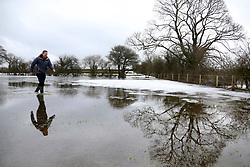 © Licensed to London News Pictures. 05/03/2018. Bodden, UK. Tim Walters walks through flood water left by melted snow, in a field in Bodden near Shepton Mallet, Somerset after a week of heavy snow. . Photo credit: Jason Bryant/LNP
