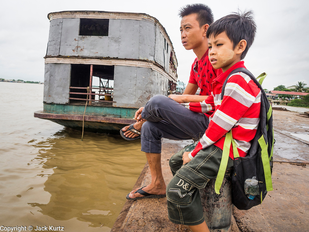 08 JUNE 2014 - YANGON, MYANMAR: A man and his son sit on a jetty on the Yangon waterfront. Yangon, Myanmar (Rangoon, Burma). Yangon, with a population of over five million, continues to be the country's largest city and the most important commercial center.      PHOTO BY JACK KURTZ