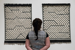 """© Licensed to London News Pictures. 09/10/2018. LONDON, UK. A visitor views """"Vicara Rug I"""" and """"Vicara Rug II"""", 1959, by Anni Albers in collaboration with Inge Brouard Brown.  Preview of the UK's first exhibition of works by German artist Anni Albers at Tate Modern who used the ancient art of hand-weaving to produce works of modern art.  Over 350 of her artworks from major collections from Europe and the US are on show 11 October to 27 January 2019.  Photo credit: Stephen Chung/LNP"""