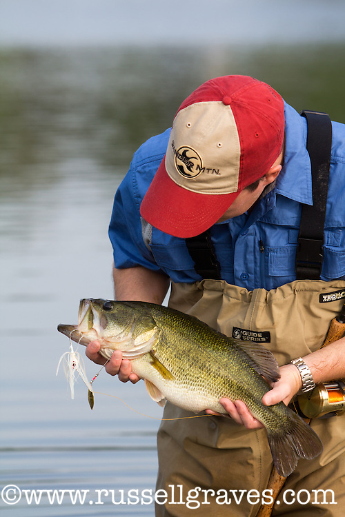 ANGLER ADMIRING A LARGEMOUTH BASS CAUGHT ON A BAITCASTING ROD USING A WHITE SPINNERBAIT