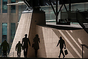 Silhouettes of Londoners walking through the Broadgate corporate offices development in the City of London. A person carries a shopping bag and others make their way towards a brighter area under the tall steel architecture with the backdrop of the Broadgate development within the ancient boundary of the capital's Square Mile, it's financial district founded by the Romans in AD43.