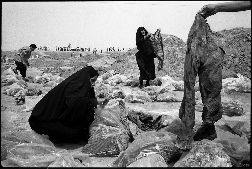 Iraqis search a mass grave site for remains in a frantic search for relatives at a mass grave near Hillah, Iraq. They check the bones and clothes for identification papers, jewelery, even cigaret packs, looking for something familiar. The destruction of evidence (of crimes against humanity and of identity) was so great that Human Rights Watch began a campaign to embarass the U.S. military into closing the site.