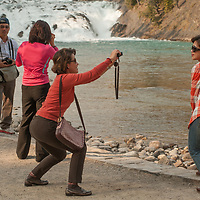 Tourists photograph each other beside Bow Falls in Banff National Park, Alberta, Canada.