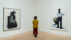 """© Licensed to London News Pictures. 02/12/2020. LONDON, UK. A staff member views (L to R) """"6pm Madeira"""", 2011, and """"Avalanche"""", 2011.  Preview of """"Lynette Yiadom-Boakye: Fly In League With The Night"""" the first major UK survey exhibition by British artist Lynette Yiadom-Boakye.  Over 70 of her works spanning two decades are on display at Tate Britain.  It is the first new exhibition at Tate since the galleries were re-opened after coronavirus lockdown restrictions were slightly eased by the UK government.  Photo credit: Stephen Chung/LNP"""
