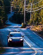 a car courses along a winding rural road in the southwestern part of the Kitsap Peninsula in Puget Sound, Washington state, USA