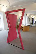 """Door. This door and its frame take an unconventional form. The door resembles two triangles which interlock to create a shape similar to a huge, upturned bow. It is narrow at its centre and with a wide upper frame and threshold. Its frame is similarly altered and both door and frame are coloured red. The door is made of plywood laminated in plastic and has a brass door knob. Measuring over two metres in height, it stands open at a forty-five degree angle, wide enough for a person to walk through. <br /><br />Michelangelo Pistoletto (born 25 June 1933) is an Italian painter, action and object artist, and art theorist. Pistoletto is acknowledged as one of the main representatives of the Italian Arte Povera. His work mainly deals with the subject matter of reflection and the unification of art and everyday life in terms of a Gesamtkunstwerk<br /><br />In 1996, he founded the art city Cittadelarte – Fondazione Pistoletto in a discarded textile factory near Biella. Its objective, in brief, is """"to inspire and produce a responsible change in society by means of creative ideas and projects."""" Nowadays Pistoletto is particularly concerned with environmental issues, and to develop awareness about using only what we need and to create awareness about over consumption."""