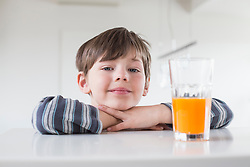 Portrait of boy with glass of juice, close up
