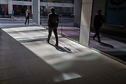 City workers walk through a covered walkway where reflected light from office plate glass leaves shadows, the capitals financial district, on 19th April, in the City of London, England.