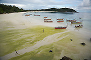 Pattaya Beach. Long tail boats stranded during low tide. Heavy rainfall caused algae growth on the beach.