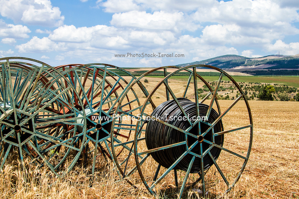 Rolled up irrigation pipes in a harvested wheat field Photographed in Galilee, Israel