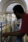 A black inmate looks over the wing outside of his cell on the top balcony of the A wing at Wandsworth Prison. HMP Wandsworth in South West London was built in 1851 and is one of the largest prisons in Western Europe. It has a capacity of 1456 prisoners.