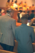 Father and son ages 55 and 14 standing up during church service. Mount Olivet Baptist Church St Paul  Minnesota USA