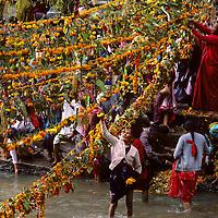 NEPAL, Kathmandu, Hindu bathers & festival garlands at Pashupatinath Temple (Bagmati River).