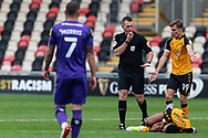 Today's referee Thomas Bramall looks at the injured Newport County's Captain Joss Labadie (4) during the EFL Sky Bet League 2 match between Newport County and Tranmere Rovers at Rodney Parade, Newport, Wales on 17 October 2020.