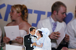 Card place setting; bride and groom in the background,