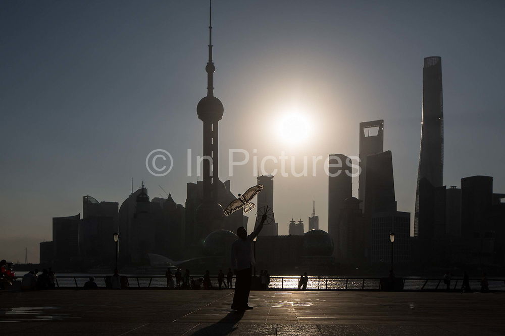A man flies a kite along the Bund while buildings of Pudongs Lujiazui financial district stand across the Huangpu River as the sun rises in Shanghai, China, on Friday, Oct. 2, 2015.