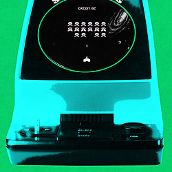 Retro Space Wars Handheld Invaders arcade game in monochrome on green textured card background